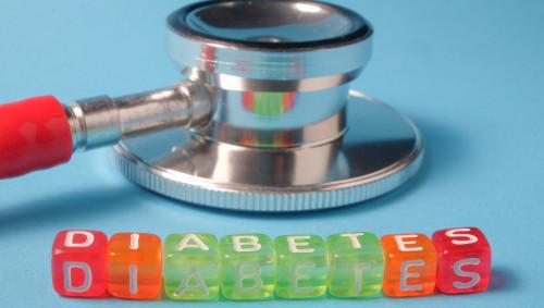 Ein Stethoskop und Buchstaben, die das Wort Diabetes bilden, auf blauem Grund.