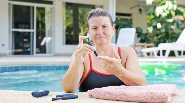 Das Bild zeigt eine Frau im Pool, die ihren Blutzucker misst.