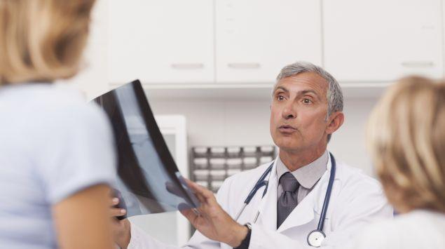 Ein Arzt mit einem Röntgenbild im Gespräch mit einer Patientin.