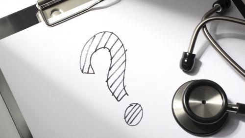 Ein Blatt Papier mit einem Fragezeichen darauf, daneben ein Stethoskop.