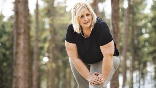 Eine übergewichtige Frau macht Dehnübungen im Grünen.