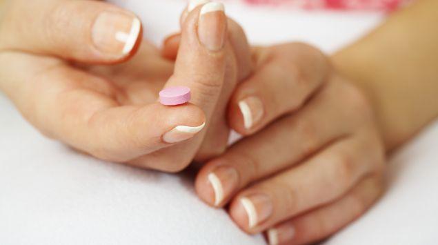 Das Bild zeigt eine Pille auf dem Zeigerfinger einer Frau.