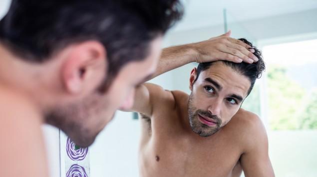 Das Bild zeigt einen jungen Mann, der vor einem Spiegel steht und seinen Haaransatz betrachtet.