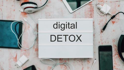 """Eine Leuchtbox mit der Aufschrift """"digital Detox"""", umgeben von verschiedenen Smartphones."""