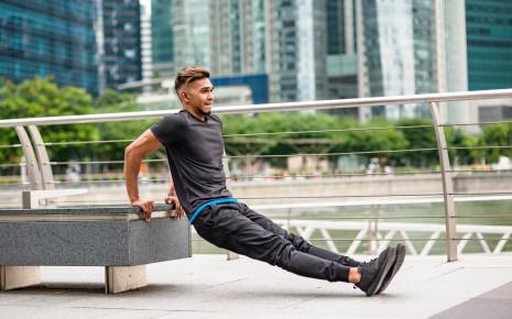Ein Mann macht eine Fitnessübung (Barrenstütz/Dip).