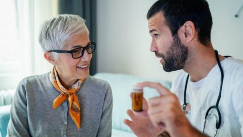 Ein Arzt hält eine Dose mit Tabletten in der Hand und spricht mit einer älteren Frau.