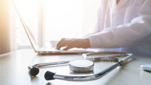 Das Bild zeigt einen Doktor, der am PC arbeitet.
