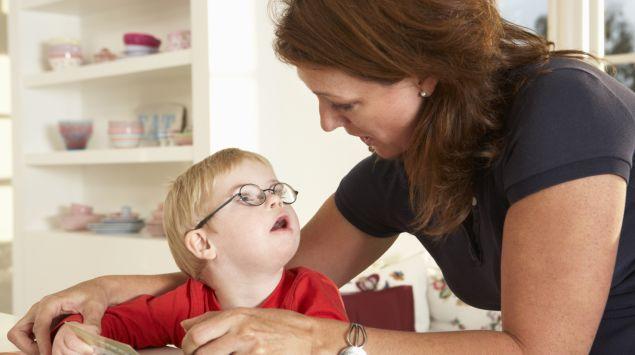 Man sieht ein Kind mit Down-Syndrom bei der Sprachtherapie.