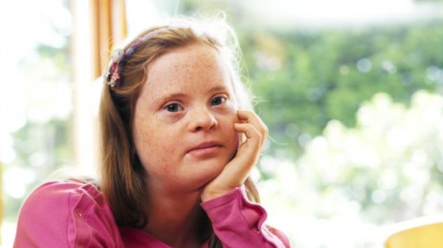 Das Bild zeigt ein Mädchen mit Down-Syndrom.