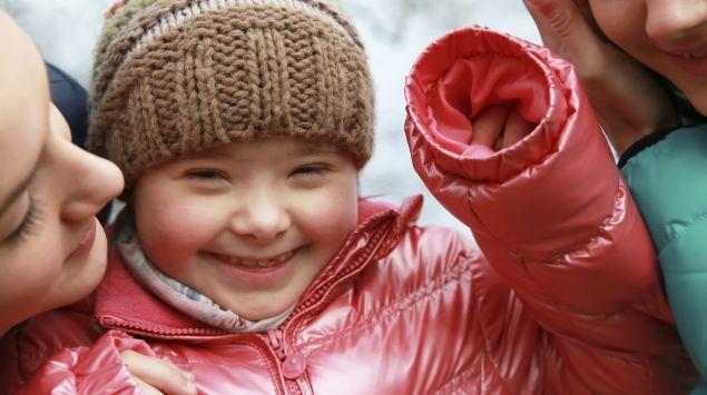 Man sieht ein Kind mit Down-Syndrom mit seiner Familie.
