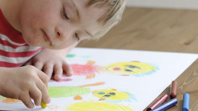 Ein Junge mit Down-Syndrom malt ein Bild.