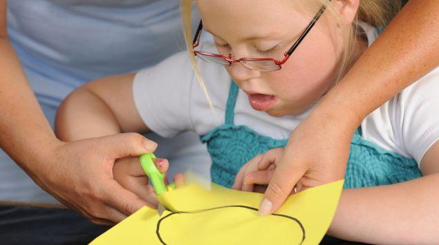 Ein Mädchen schneidet mit Unterstützung einen Kreis aus Papier aus.