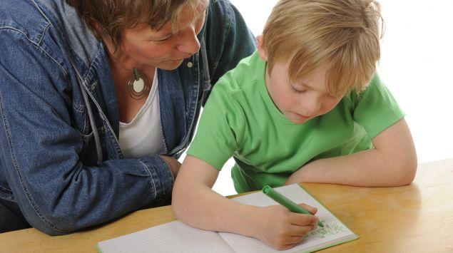 Man sieht einen Jungen mit Down-Syndrom bei Schreibübungen.