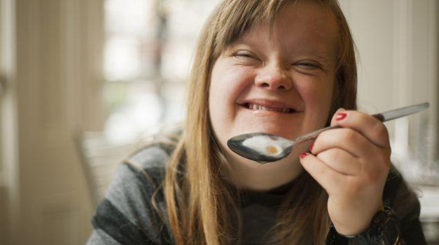 Man sieht eine junge Frau mit Down-Syndrom beim Essen.
