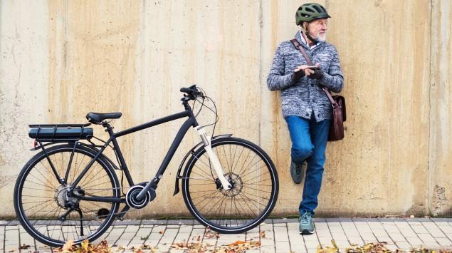 Ein älterer Mann neben einem E-Bike: Wer erstmals aufs Elektrofahrrad steigen möchte, sollte ein paar Tipps beachten.