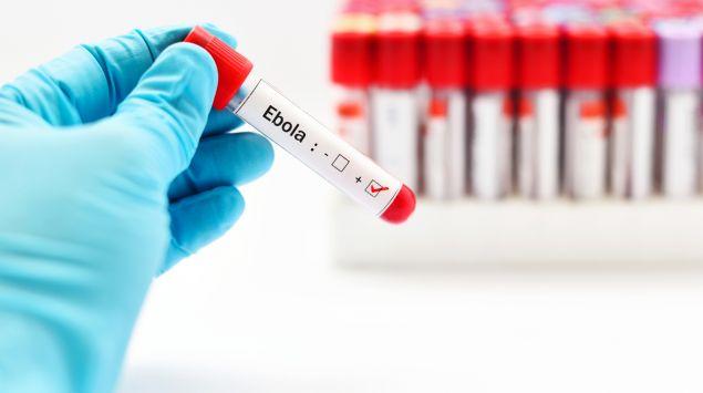 Jeman hält ein Teströhrchen mit der Aufschrift Ebola in der Hand.
