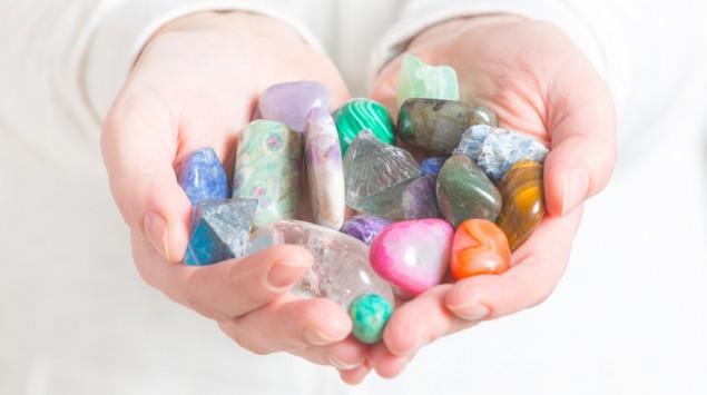 Jemand hält verschiedene Edelsteine in den Händen.