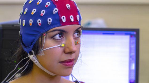 Das Bild zeigt eine Frau mit einer EEG-Haube auf dem Kopf-