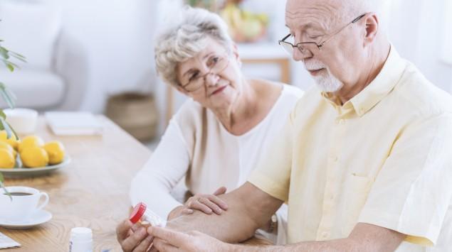 Ein älterer Mann betrachtet eine Tabletten-Dose.