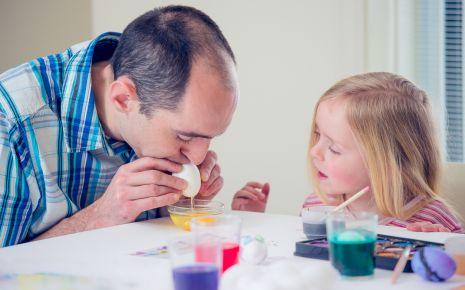 Ostereier: Ein Mann bläst Eier aus, ein kleines Mädchen schaut zu.