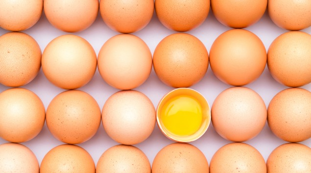 Eier liegen in der Draufsicht nebeneinander, eines ist geöffnet