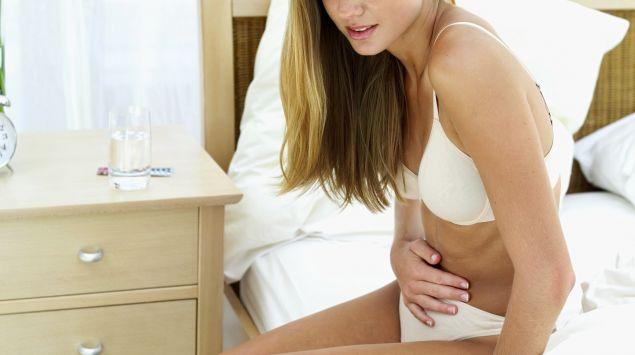 Das Bild zeigt eine Frau auf einem Bett, die vor Schmerzen ihren Bauch hält.