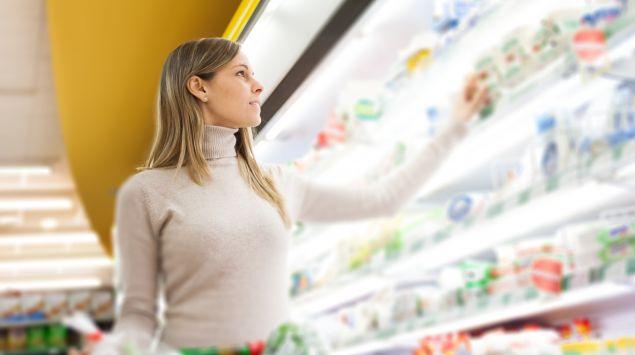 Eine Frau steht vor einem Kühlregal im Supermarkt.