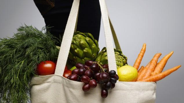 Jemand trägt eine Einkaufstasche mit Obst und Gemüse.