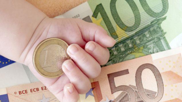 Babyhand mit Euroscheinen und Münze