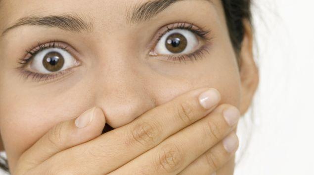 Frau hält sich den Mund zu und schaut erschrocken