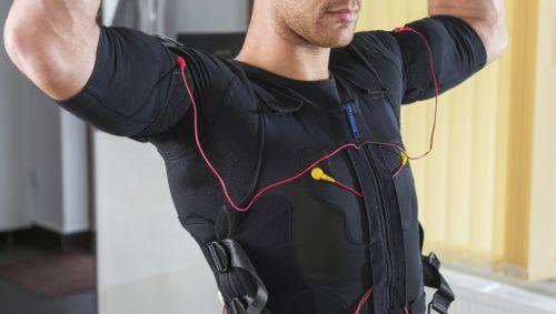 EMS-Training: Ein Mann im Elektrodenanzug macht Übungen mit Hanteln.