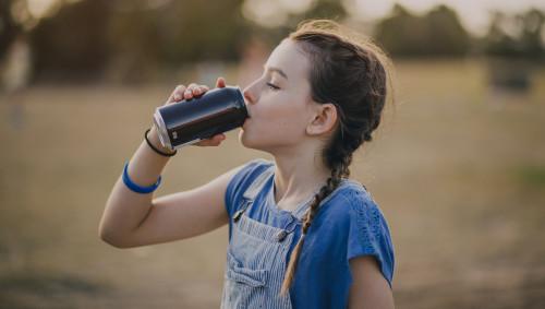 Ein junges Mädchen trinkt aus einer Dose