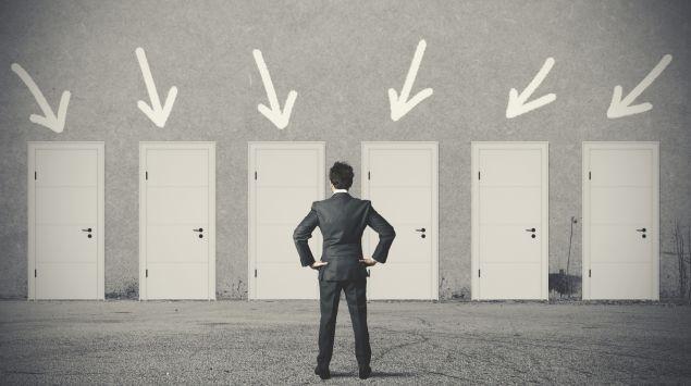 Das Bild zeigt einen Mann, der vor mehreren Türen steht und sich für eine entscheiden muss.