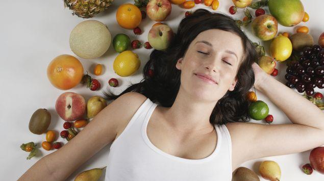 Man sieht eine Frau, die mit geschlossenen Augen zwischen Obst liegt.