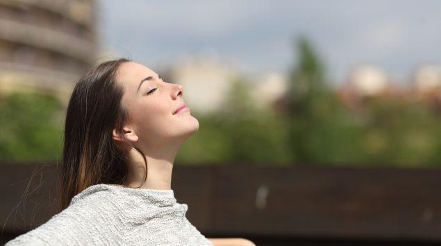 Das Bild zeigt eine junge Frau, die auf einer Bank sitzt und die Sonne genießt.