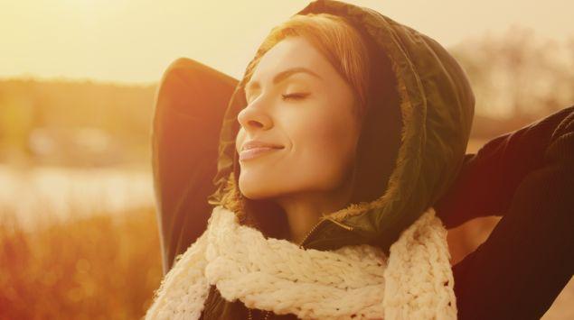 Eine Frau verschränkt die Arme hinter dem Kopf und schaut mit geschlossenen Augen ins Sonnenlicht.