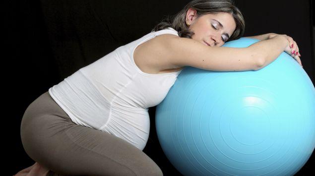 Schwangere lehnt Oberkörper zur Entspannung auf einen Gymnastikball.