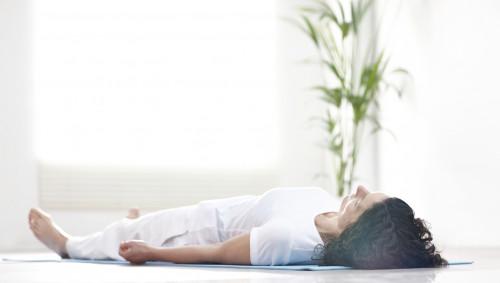 Eine Frau macht eine Entspannungsübung auf dem Boden.