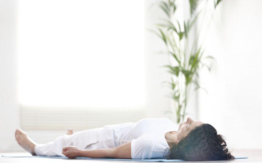 Tinnitus: Ein Frau liegt auf einer Matte auf dem Rücken.