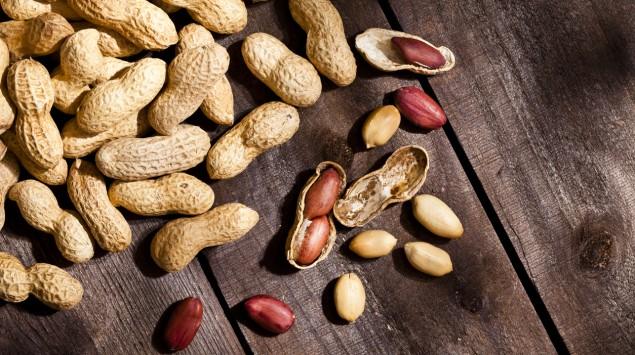 Auf einem Tisch liegt ein Haufen ungeschälter und geschälter Erdnüsse.