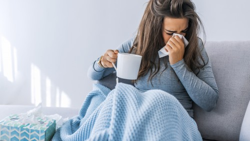 Man sieht eine erkältete Frau, die eine Teetasse hält und sich die Nase putzt.