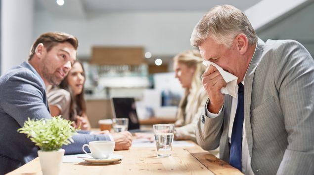 Eine Gruppe Menschen sitzt am Tisch, im Vordergrund niest ein Mann in ein Taschentuch.
