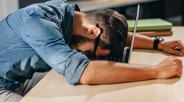 Ein Mann liegt mit dem Kopf auf der Tastatur eines Laptops.