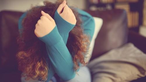 Ein Frau sitzt auf einem Sofa und hat ihren Kopf in den Armen vergraben.