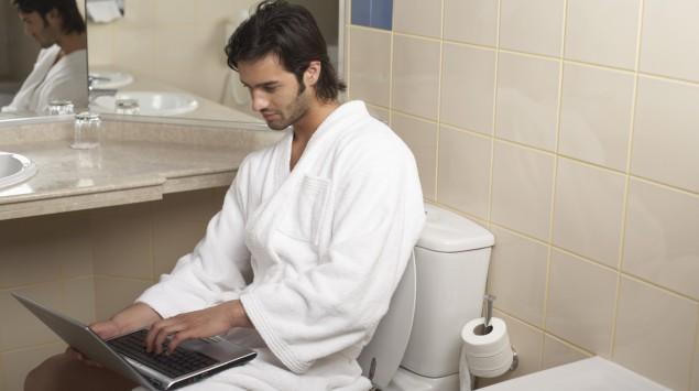 Ein Mann sitzt mit seinem Laptop auf der Toilette.