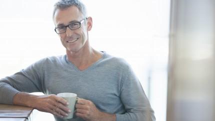 Un hombre maduro tomando un café.