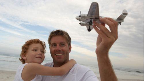 padre e hijo en la playa jugando con un avión