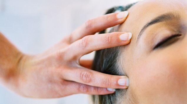 Una mujer recibiendo un masaje de cabeza.