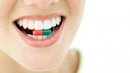 Una mujer con una pastilla en la boca.