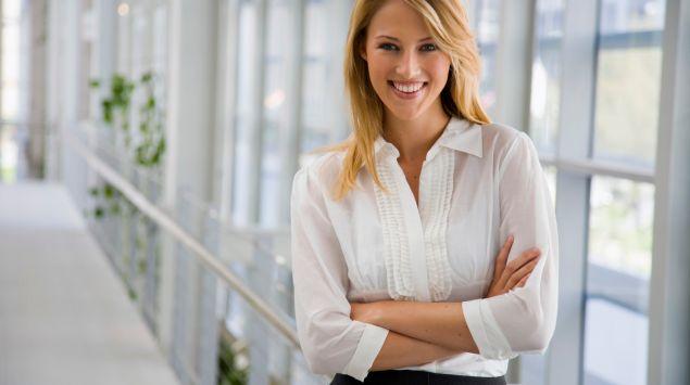 Una mujer rubia con camisa blanca.